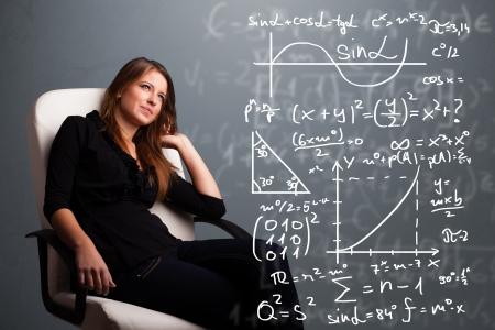 signos matematicos: Hermosa joven de la escuela piensa la chica acerca de los signos matem?ticos complejos Foto de archivo