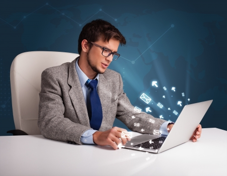 Attractive young man sitting at dest and typing on laptop with message icons comming out Stock Photo - 19664415