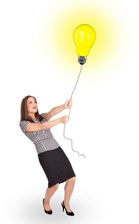 Happy young woman holding a light bulb balloon photo