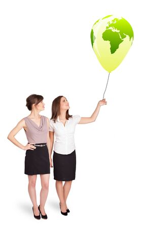 Happy young ladies holding a green globe balloon photo