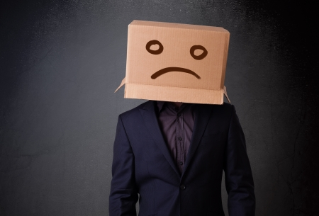 masquerader: Young man standing with a brown cardboard box on his head with sad face Stock Photo