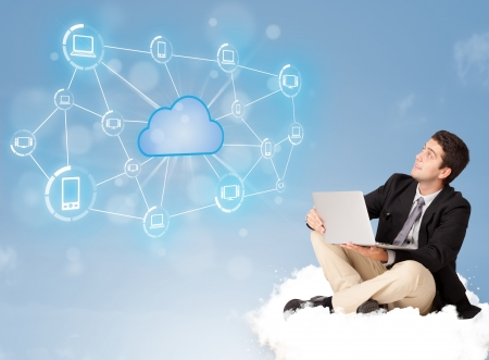 Happy young businessman sitting on cloud with cloud computing photo