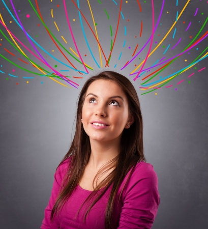 Pretty young girl thinking with colorful abstract lines overhead Stock Photo - 19789573