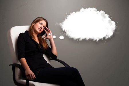 Pretty young lady thinking about cloud speech or thought bubble with copy space photo
