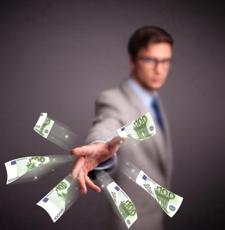 billets euros: Beau jeune homme debout et jeter de l'argent Banque d'images