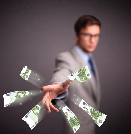 Handsome young man standing and throwing money Stock Photo - 19789506