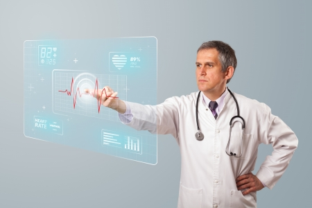 the medic: Middle aged doctor standing and pressing modern medical type of button Stock Photo
