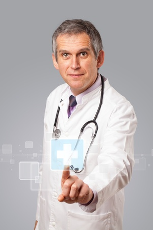 medical symbol: Middle aged doctor pressing modern medical type of button