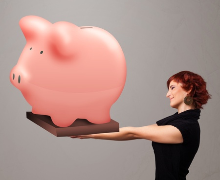Beautiful young girl holding a huge savings piggy bank photo