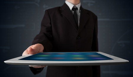 Young businessman holding a white modern tablet with blurry apps photo