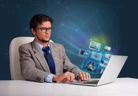 Attractive young man sitting at desk and watching his photo gallery on laptop Stock Photo - 20524011