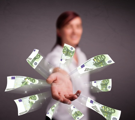 Pretty young woman standing and throwing money Stock Photo - 20524012