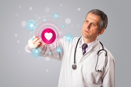 Middle aged doctor standing and pressing modern medical type of button photo