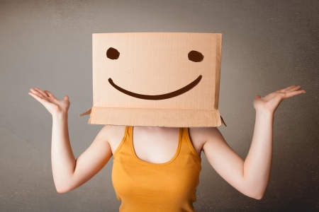 female mask: Young lady standing and gesturing with a cardboard box on her head with smiley face