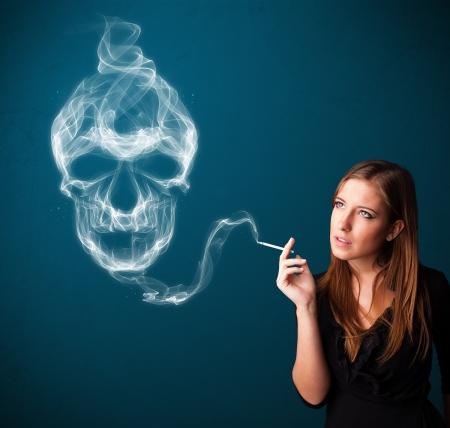 smoking: Pretty young woman smoking dangerous cigarette with toxic skull smoke
