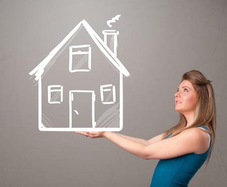 巨大な引かれた家を保持している美しい若い女性 写真素材