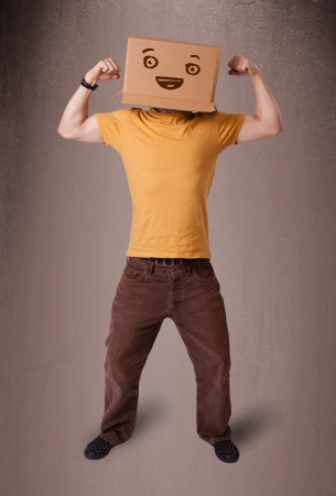 hiding face: Young man standing and gesturing with a cardboard box on his head with smiley face