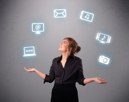 pretty girl standing and juggling with elecrtonic devices icons photo
