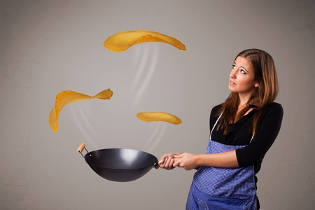 Beautiful young woman making pancakes photo