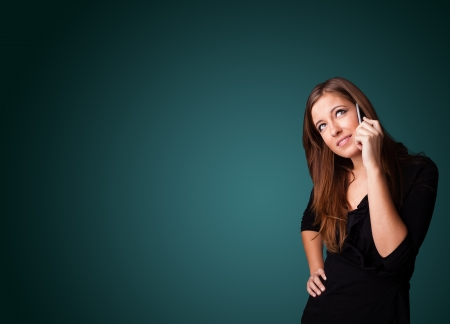 Young woman standing and making phone call with copy space photo
