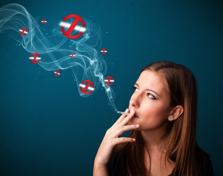 Beautiful young woman smoking dangerous cigarette with no smoking signs photo