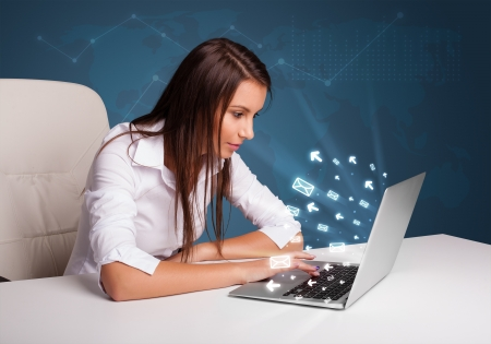 internet business: Pretty young lady sitting at dest and typing on laptop with message icons comming out