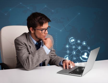 Attractive young man sitting at desk and typing on laptop with social network icons comming out photo