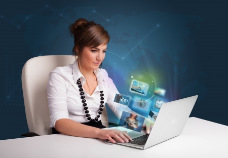 Beautiful young girl sitting at desk and watching her photo gallery on laptop Stock Photo - 20687248