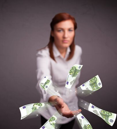 Pretty young woman standing and throwing money Stock Photo - 20685591