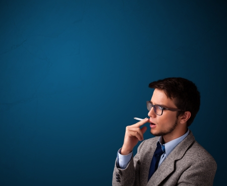 Handsome young man smoking cigarette with copy space photo