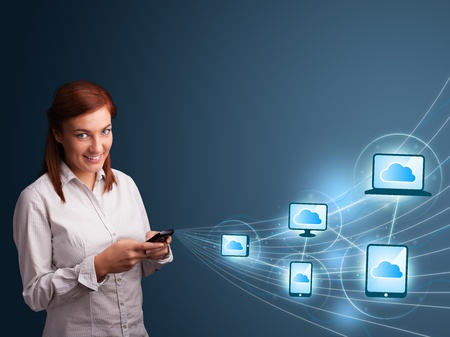 Pretty young lady typing on smartphone with cloud computing photo