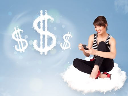 Pretty young woman sitting on cloud next to cloud dollar signs photo
