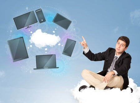 Happy young businessman sitting on cloud enjoying cloud network service photo