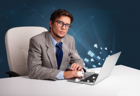 Attractive young man sitting at dest and typing on laptop with message icons comming out Stock Photo - 20836950