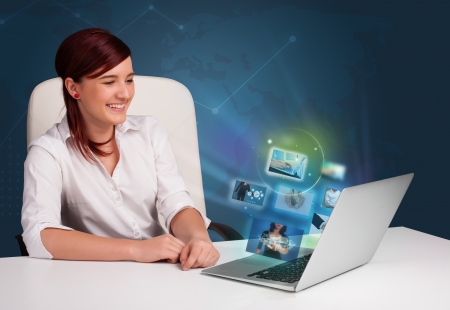 Beautiful young girl sitting at desk and watching her photo gallery on laptop Stock Photo - 20836957