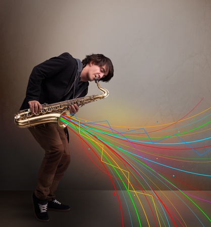 Attractive young musician playing on saxophone while colorful abstract lines exploding photo