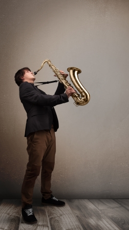 Handsome young musician playing on saxophone photo
