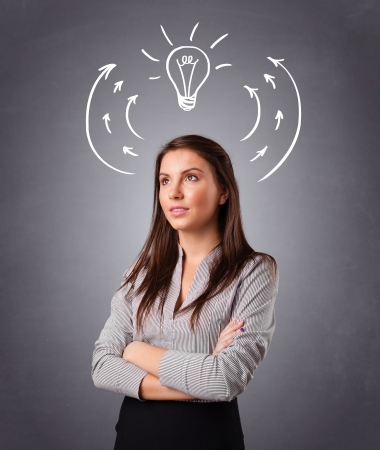 Pretty young lady standing and thinking with arrows and light bulb overhead photo