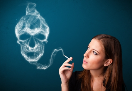 Pretty young woman smoking dangerous cigarette with toxic skull smoke  Stock Photo - 21017392
