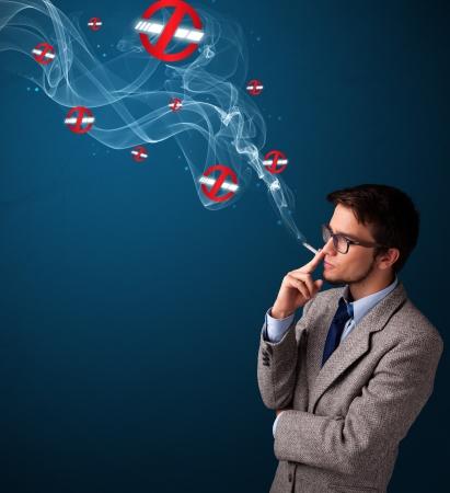 malos habitos: Atractivo joven peligroso fumar cigarrillos con muestras de no fumadores Foto de archivo
