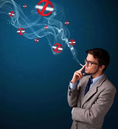 man smoking: Attractive young man smoking dangerous cigarette with no smoking signs Stock Photo