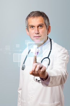 Middle aged doctor pressing modern medical type of button photo