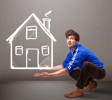 Attractive young boy holding a huge drawn house photo