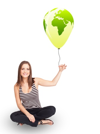 Happy young lady holding a green globe balloon Stock Photo - 21017997