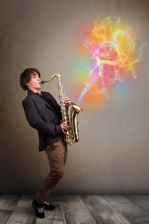 Attractive young musician playing on saxophone with colorful abstract fume comming out photo