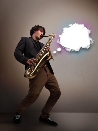 Handsome young man playing on saxophone with copy space in white cloud photo