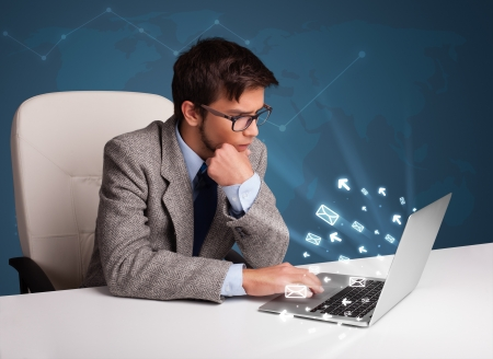 Attractive young man sitting at dest and typing on laptop with message icons comming out photo