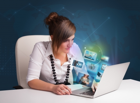 Beautiful young girl sitting at desk and watching her photo gallery on laptop Stock Photo - 21160897