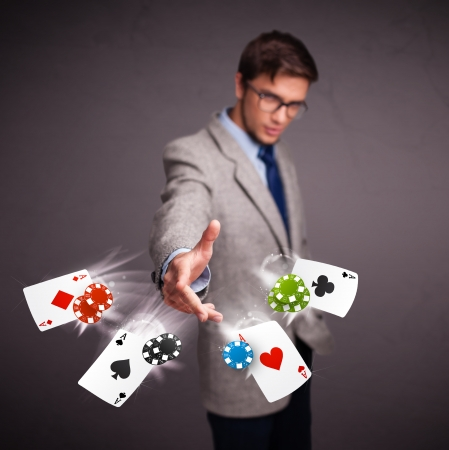 play card: Handsome young man playing with poker cards and chips Stock Photo