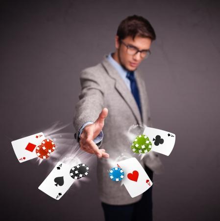 Knappe jonge man spelen met poker kaarten en chips